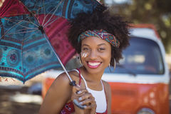 Portrait of happy woman holding umbrella. Against van on field Stock Photos