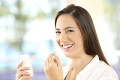 Happy woman holding a pill and bottle. Portrait of a happy woman holding a vitamins pill and bottle Royalty Free Stock Image