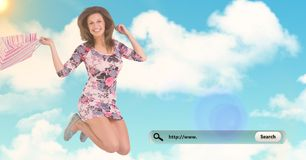 Portrait of happy woman jumping with shopping bag. Against digitally generated sky background Royalty Free Stock Photos