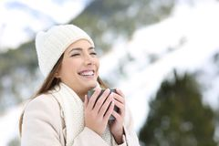 Woman keeping warm holding a cup of coffee in winter. Portrait of a happy woman keeping warm holding a cup of coffee in winter holidays in the snowy mountain stock photography
