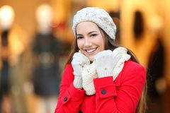 Woman keeping warm in winter in a mall. Portrait of a happy woman keeping warm in winter in a mall in winter Stock Images