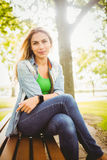 Portrait of happy woman with legs crossed at park Stock Photo