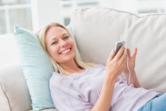 Portrait of happy woman listening music at home Royalty Free Stock Images