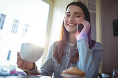 Portrait of happy woman listening to cellphone at cafe Stock Photos