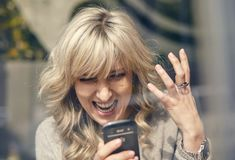Portrait of a happy woman looking at the phone. And very joyful Stock Images