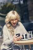 Portrait of a happy woman looking at the phone. And very joyful Royalty Free Stock Photo