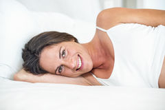 Portrait of happy woman lying on bed Royalty Free Stock Image