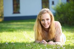 Portrait of a happy woman lying on grass outdoors Royalty Free Stock Image