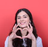 Portrait of happy woman making heart shape with hands against re Stock Photos