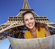 Portrait of happy woman with map against Eiffel tower, Paris. Touristy, without doubt, but yet so fun. Portrait of happy young woman with map against Eiffel Stock Photography