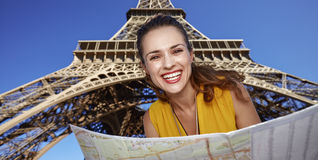 Portrait of happy woman with map against Eiffel tower, Paris. Touristy, without doubt, but yet so fun. Portrait of happy young woman with map against Eiffel Stock Image