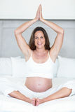 Portrait of happy woman meditating. Portrait of happy pregnant woman meditating on bed in house Stock Photography