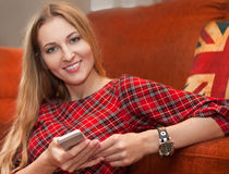 Portrait of happy woman with mobile phone sitting on floor at ho Stock Photos