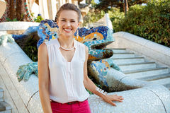 Portrait of happy woman near mosaic dragon in Park Guell, Spain Stock Photo