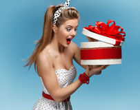 Portrait of happy woman opening gift box against blue background. Holidays, holiday, celebration, birthday and happiness concept Stock Photo