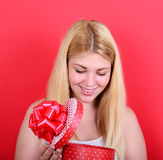 Portrait of happy woman opening gift box against red background Stock Photos