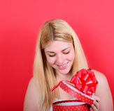 Portrait of happy woman opening gift box against red background Royalty Free Stock Image