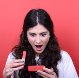 Portrait of happy woman opening gift box against red background Stock Image