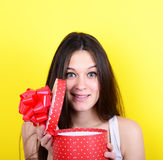 Portrait of happy woman opening gift box against yellow backgrou Stock Photo
