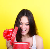 Portrait of happy woman opening gift box against yellow backgrou Stock Photography