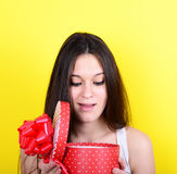 Portrait of happy woman opening gift box against yellow backgrou Royalty Free Stock Image