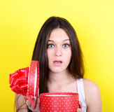 Portrait of happy woman opening gift box against yellow backgrou Royalty Free Stock Photography