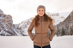 Portrait of happy woman outdoors among snow-capped mountains Stock Photo