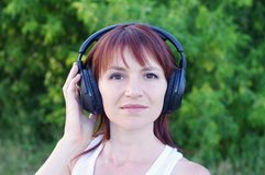 Portrait of happy woman outdoors in wireless headset Royalty Free Stock Image