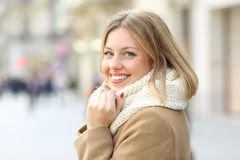 Happy woman posing looking at camera in winter in the street stock images