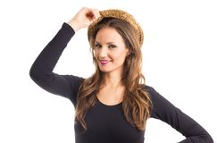Happy woman puts hat on head. Person with green eyes and blonde. Portrait of happy woman putting a panama hat on the head. Person wears black and casual clothes royalty free stock photos