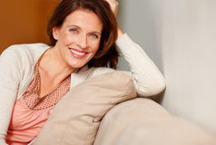 Portrait of happy woman relaxing on a couch Royalty Free Stock Image