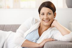 Portrait of happy woman resting at home. Lying on couch, smiling Royalty Free Stock Photo