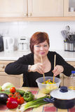 Portrait of happy woman with salad. Middle aged woman posing with vegetable salad in kitchen Stock Image