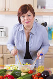 Portrait of happy woman with salad. Middle aged woman posing with vegetable salad in kitchen Stock Images