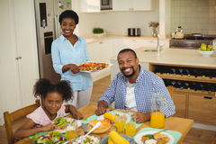 Portrait of happy woman serving food to the family Stock Photography