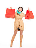 Portrait of happy woman with shopping bags in autumn coat Stock Images