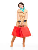 Portrait of happy woman with shopping bags in autumn coat Royalty Free Stock Images