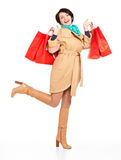 Portrait of happy woman with shopping bags in autumn coat Stock Photo
