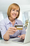Portrait of happy woman shopping online at home during Christmas Stock Images