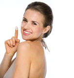 Portrait of happy woman showing creme on finger Stock Photos