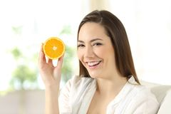 Woman showing half orange at home. Portrait of a happy woman showing half orange sitting on a couch in the living room at home Royalty Free Stock Image
