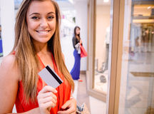 Portrait of happy woman showing her credit card outside a shop Stock Photography