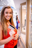 Portrait of happy woman showing her credit card outside a shop Stock Image