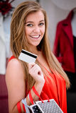 Portrait of happy woman showing her credit card while shopping Stock Images