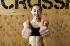 Portrait of happy woman showing her thumbs up at gym royalty free stock photos