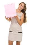 Portrait of happy woman showing pink shopping bag. Portrait of happy young woman showing pink shopping bag Stock Image