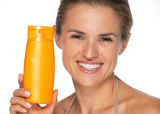 Portrait of happy woman showing sun screen bottle Royalty Free Stock Images
