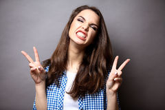 Portrait of a happy woman showing victory with Royalty Free Stock Images