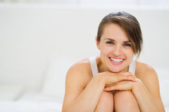 Portrait of happy woman sitting on bed Royalty Free Stock Images