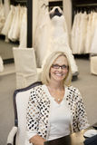 Portrait of a happy woman sitting on chair in bridal store Stock Photo